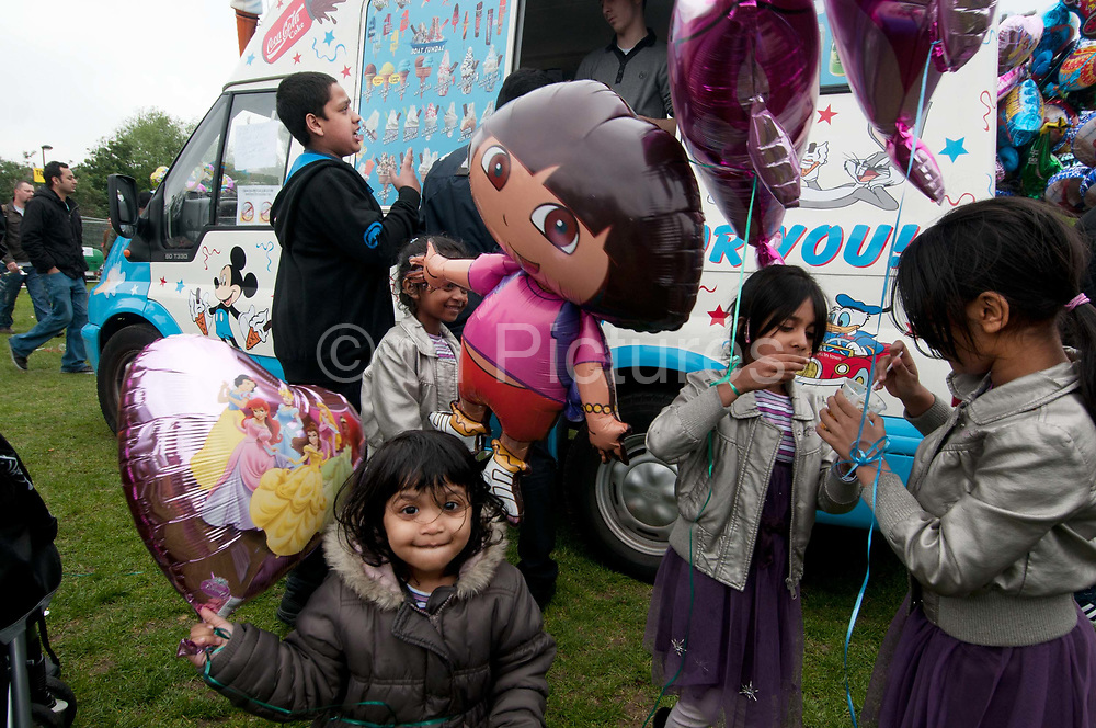 Weavers Fields, Bethnal green, London. Boishakhi Mela, celebration for Bangladesh New Year. Father buying icecream for his children who also have balloons