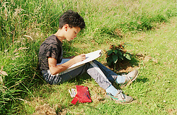 Junior school boy sitting on grass in field holding clipboard and writing notes for biology fieldwork research project,