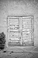 Black and white image of a rustic doorway in San Quirico d'Orcia, Italy.