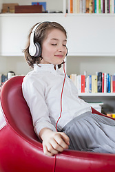 Girl sitting on chair and listening music with headset