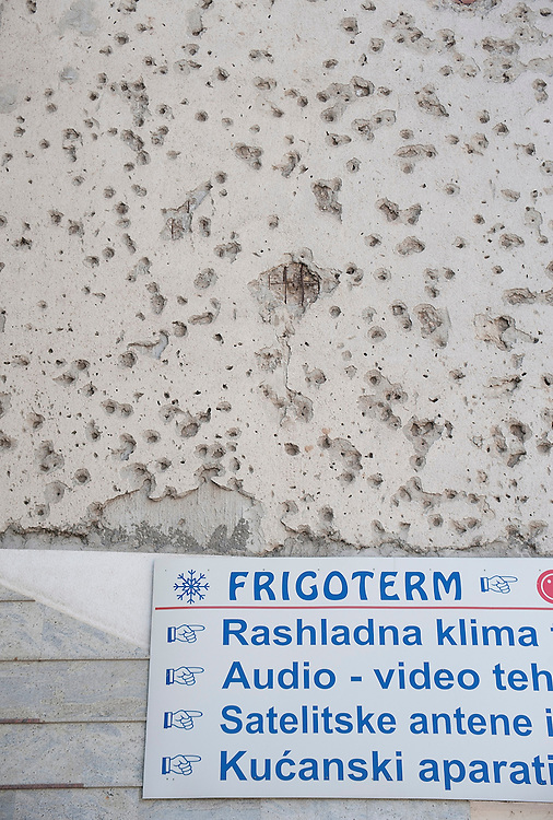 MOSTAR, BOSNIA AND HERZEGOVINA - JUNE 28:  A new advert sign is seen a concrete wall damaged by bulletts from the 1993 war is seen on June 28, 2013 in Mostar, Bosnia and Herzegovina. The Siege of Mostar reached its peak and more cruent time during 1993. Initially, it involved the Croatian Defence Council (HVO) and the 4th Corps of the ARBiH fighting against the Yugoslav People's Army (JNA) later Croats and Muslim Bosnian began to fight amongst each other, it ended with Bosnia and Herzegovina declaring independence from Yugoslavia.  (Photo by Marco Secchi/Getty Images)