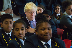 Michaela Community School, Wembley, London, June 23rd 2015. Mayor of London Boris Johnson visits the Michaela Community School, a Free School in Wembley that started taking students in September2014 after battling a certain amount of resistance from locals and unions. During the visit Head Teacher Katharine Birbalsingh took the Mayor on a tour of the school before he participated in a history lesson, prior to sitting down with pupils for brunch. PICTURED: Back to school. Sitting with the students at brunch, he mayor gives his attention to the Head Teacher.