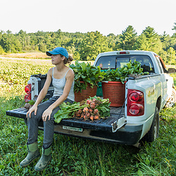 A farm worker takes a break in her pickup during a beet harvest on a farm on Kinney Hill in South Hampton, New Hampshire.