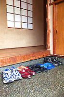 The Genkan is a traditional Japanese entrance for a house or apartment. The main function of a genkan is for the removal of shoes before entering the main part of the house.  Shoes are usually turned to face the door so they can easily be slipped on when leaving or placed into a getabako or shoe box/shoe closet.