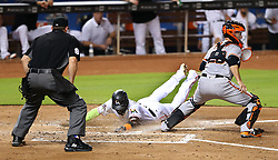 August 15, 2017 - Miami, FL, USA - San Francisco Giants catcher Buster Posey, right, waits for a throw as the Miami Marlins' Marcell Ozuna slides safely at home plate after a sacrifice fly by J.T.Realmuto in the first inning at Marlins Park in Miami on Tuesday, Aug. 15, 2017. (Credit Image: © Pedro Portal/TNS via ZUMA Wire)