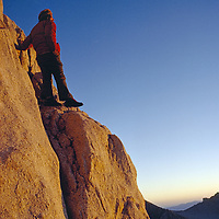 John Muir Wilderness, Sierra Nevada, California.A mountaineer watches dawn break after bivouac on a mountain ledge.color image,photography,outdoors,day,one person,men,unrecognizable person,standing,watching,dawn,low angle view,mountain climbing,mountaineer,climbing,sport,athlete,relaxation,morning,full length,rear view,sunrises,sky,cliffs,mountains,rock,keeler needle,john muir wilderness area,sierra nevada mountains,california,camps,camping,inyo national forest,adventure bivouac,inyo county,adventure,copy space