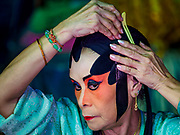 """26 FEBRUARY 2018 - BANGKOK, THAILAND: A performer puts on parts of a costume before a Chinese Opera at the Phek Leng Shrine in the Khlong Toey section of Bangkok. The shrine traditionally hosts a Chinese Opera just after the end of Lunar New Year festivities. Thailand is home to the largest population of overseas Chinese in the world, and Chinese cultural practices, like Chinese opera, called """"ngiew"""" in Thailand, are popular. Many of the performers are ethnic Thais who don't speak Chinese. They learn their lines phonetically.   PHOTO BY JACK KURTZ"""