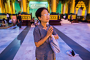 15 JUNE 2013 - YANGON, MYANMAR: A woman prays at Shwedagon Pagoda. The Shwedagon Pagoda is officially known as Shwedagon Zedi Daw and is also called the Great Dagon Pagoda or the Golden Pagoda. It is a 99 metres (325 ft) tall pagoda and stupa located in Yangon, Burma. The pagoda lies to the west of on Singuttara Hill, and dominates the skyline of the city. It is the most sacred Buddhist pagoda in Myanmar and contains relics of the past four Buddhas enshrined: the staff of Kakusandha, the water filter of Koṇāgamana, a piece of the robe of Kassapa and eight strands of hair fromGautama, the historical Buddha. The pagoda was built between the 6th and 10th centuries by the Mon people, who used to dominate the area around what is now Yangon (Rangoon). The pagoda has been renovated numerous times through the centuries. Millions of Burmese and tens of thousands of tourists visit the pagoda every year, which is the most visited site in Yangon.    PHOTO BY JACK KURTZ