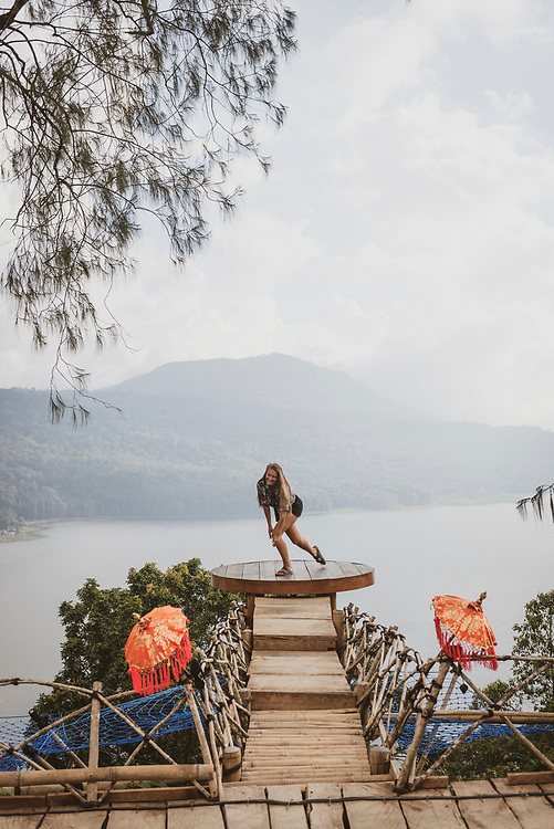Bali, Indonesia - September 22, 2017: A young woman visiting Bali does a twirl while enjoying the beautiful view from a platform high above Lake Buyan.