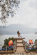A young woman visiting Bali does a twirl while enjoying the beautiful view from a platform high above Lake Buyan.