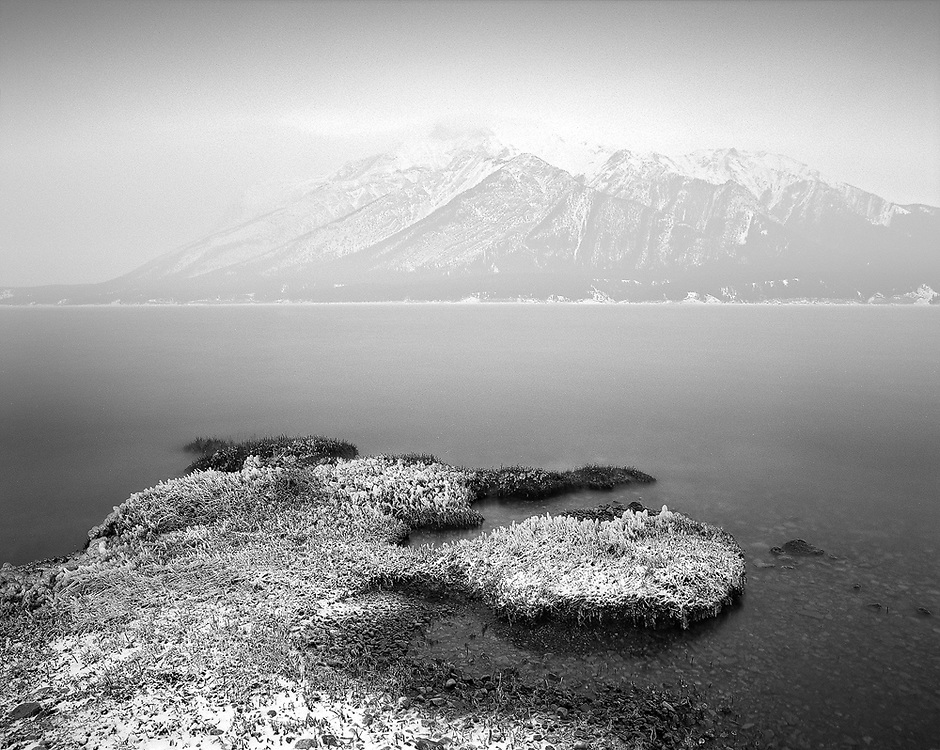 A beautiful shoreline in front of Mount Michener on a foggy day at Abraham Lake