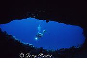 scuba diver peers through arch at Poland Cave, Christmas ( Kiritimati ) Island, Line Islands, Republic of Kiribati ( Central Pacific )