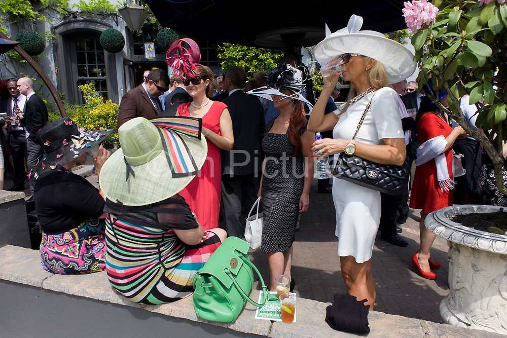 Ladies in hats enjoy a morning society drinks bar people during the annual Royal Ascot horseracing festival in Berkshire, England. Royal Ascot is one of Europe's most famous race meetings, and dates back to 1711. Queen Elizabeth and various members of the British Royal Family attend. Held every June, it's one of the main dates on the English sporting calendar and summer social season. Over 300,000 people make the annual visit to Berkshire during Royal Ascot week, making this Europe's best-attended race meeting with over £3m prize money to be won.