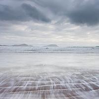 Irish rainy bad weather day at irish southwest Atlantic coast Reenroe Beach (blue flag) near Ballinskelligs with grey sky and moving waves. County Kerry, Iveragh Peninsula Ireland  / bs030