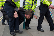 A Climate Change activist with Extinction Rebellion is arrested while campaigning for a better future for planet Earth after blocking Waterloo Bridge and as part of a multi-location 5-day Easter protest around the capital, on 16th April 2019, in London, England.