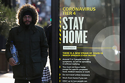 © Licensed to London News Pictures. 02/01/2021. London, UK. A man in north London walks past the government's 'Coronavirus Tier 4 - Stay Home' publicity campaign poster, after the mutated variant of the SARS-Cov-2 virus continues to spread around the country. The President of the Royal College of Physicians,Professor Andrew Goddard, has warned that COVID-19 infection cases are set to rise in the coming weeks and that NHS staff and healthcare workers are worried about the challenges against the virus over the coming months. Photo credit: Dinendra Haria/LNP