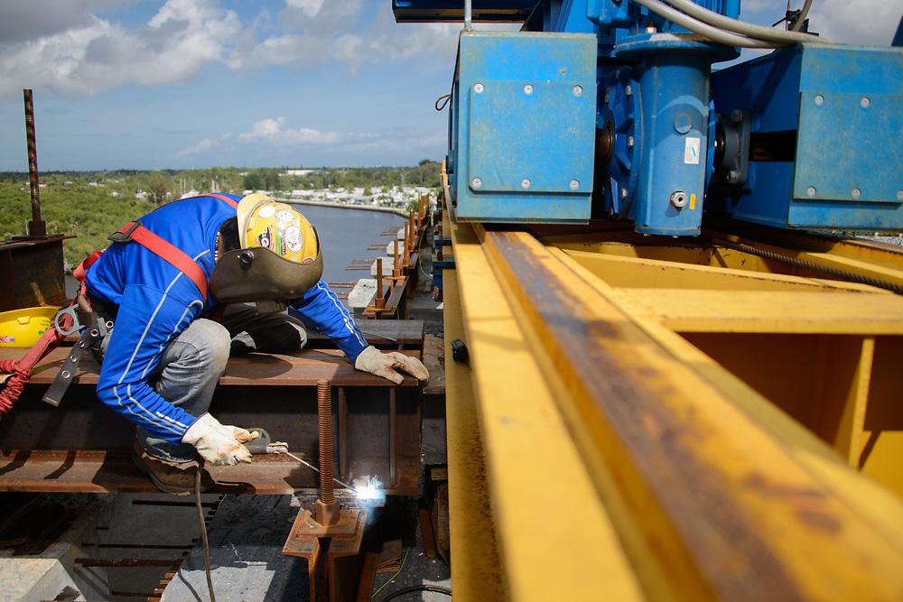 Welder on top of the Veterans Memorial Bridge during construcition.