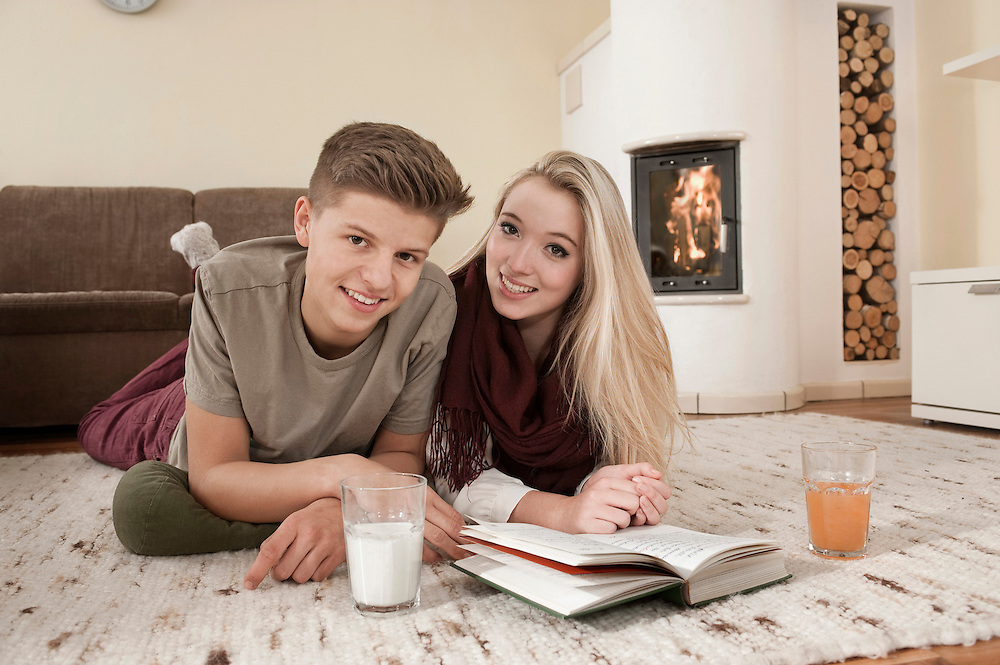 Teenage couple with book lying on carpet in front of fireside