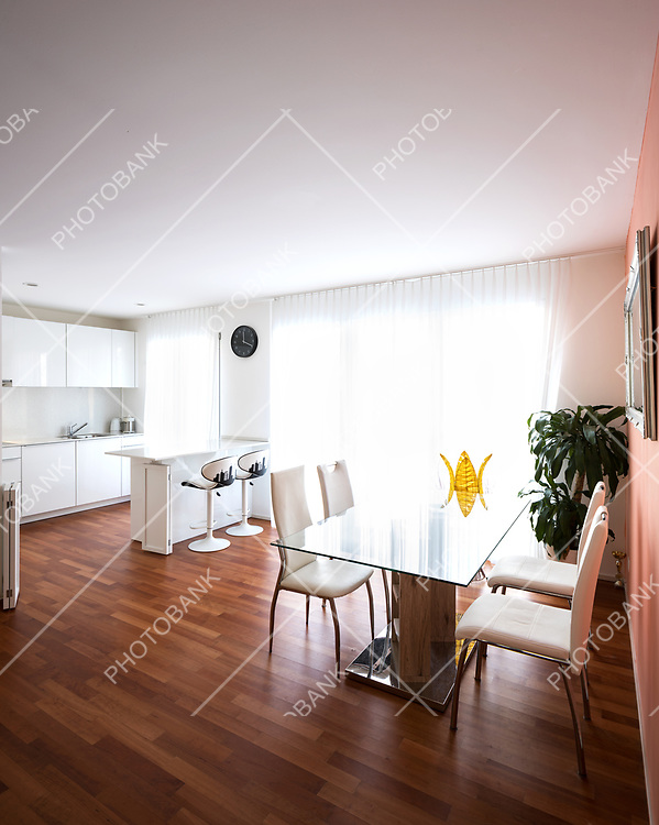 Dining room with glass table and leather chairs. Parquet and bright windows