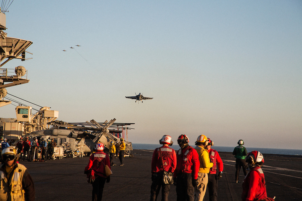 """An F/A-18 Hornet on final approach to the flight deck while another flight of three planes prepares to make the """"break"""", a final turn over the ship before landing<br /> <br /> Aboard the USS Harry S. Truman operating in the Persian Gulf. February 25, 2016.<br /> <br /> Matt Lutton / Boreal Collective for Mashable"""