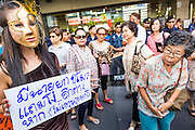 """09 JUNE 2013 - BANGKOK, THAILAND:   A White Mask protester dressed as Thai Prime Minister Yingluck Shinawatra walks through the crowd at Central World in Bangkok Sunday. The White Mask protesters wear the Guy Fawkes mask popularized by the movie """"V for Vendetta"""" and the protest groups Anonymous and Occupy. Several hundred members of the White Mask movement gathered on the plaza in front of Central World, a large shopping complex at the Ratchaprasong Intersection in Bangkok, to protest against the government of Thai Prime Minister Yingluck Shinawatra. They say that her government is corrupt and is a """"puppet"""" of ousted (and exiled) former PM Thaksin Shinawatra. Thaksin is Yingluck's brother. She was elected in 2011 when her brother endorsed her.    PHOTO BY JACK KURTZ"""