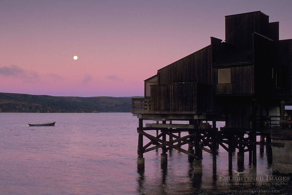 Wooden house on stilts over water and full moon set at dawn, Tomales Bay, Marin County, California