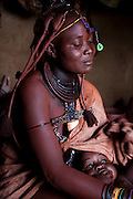 Viahondjera Musutua, a Himba woman who lives in the small village of Ondjete in northwestern Namibia, sits in her hut with her son. (Viahondjera Musutua is featured in the book What I Eat: Around the World in 80 Diets.) MODEL RELEASED.