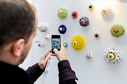 © Licensed to London News Pictures. 08/04/2016. London, UK. A visitor takes a photo of works representing eyes by Myung Nam An. The leading international fair for contemporary ceramics, Ceramic Art London 2016, opens at its new venue of Central Saint Martins, King's Cross.  88 emerging and established ceramicists from around the world are presenting and their latest works for sale to the public with prices ranging from £30 to £10,000. Photo credit : Stephen Chung/LNP