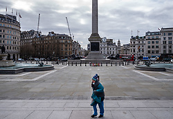 © Licensed to London News Pictures. 20/03/2020. London09.38, UK. A women wraps up against the cold in a deserted Trafalgar Square on the first day of Spring which would normally be teaming with tourists and workers now resembles a ghost town as the Coronavirus crisis continues. Photo credit: Alex Lentati/LNP