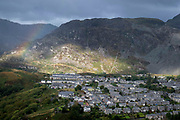With slate mountains dominating above, an aerial view of a rainbow and houses in the industrial revolution-era town of Blaenau Ffestiniog, on 5th October 2021, in Blaenau Ffestiniog, Gwynedd, Wales. The derelict slate mines around Blaenau Ffestiniog in north Wales were awarded UNESCO World Heritage status in 2021. The industry's heyday was the 1890s when the Welsh slate industry employed approximately 17,000 workers, producing almost 500,000 tonnes of slate a year, around a third of all roofing slate used in the world in the late 19th century. Only 10% of slate was ever of good enough quality and the surrounding mountains now have slate waste and the ruined remains of machinery, workshops and shelters have changed the landscape for square miles.