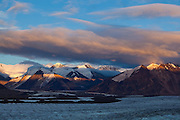 View of distant glaciated peaks up the Russell Glacier at sunset on a backpacking trip in the Skolai Pass area of Wrangell-St. Elias National Park, Alaska.