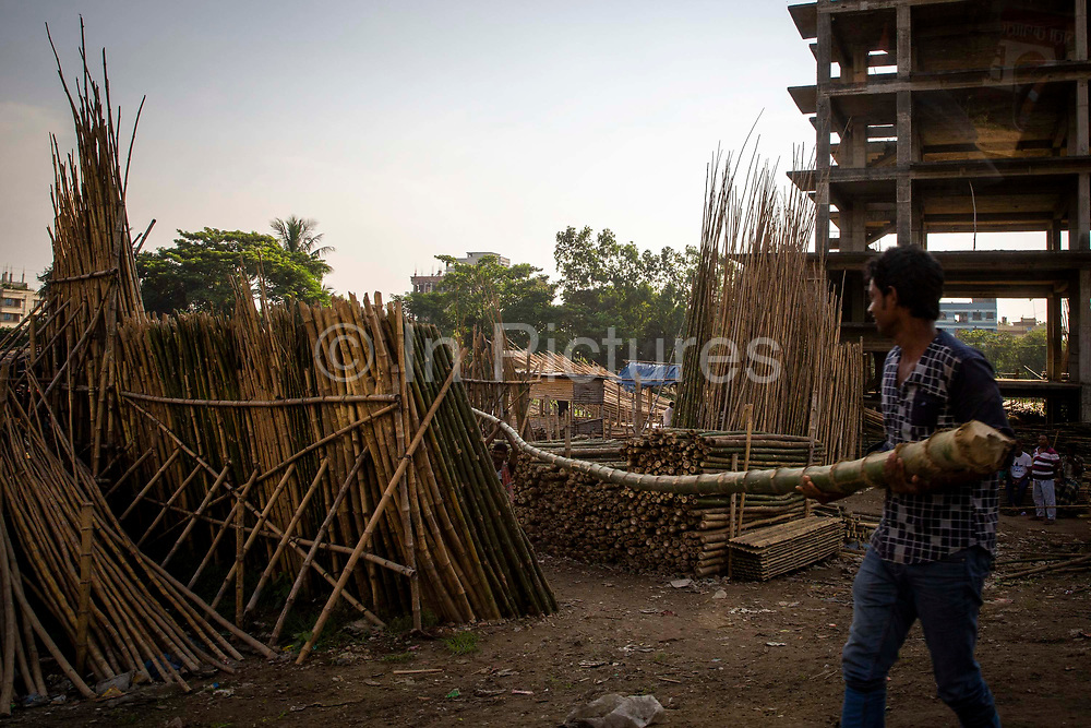 A man unloading bamboo that is used as scaffolding for building works at a yard next to Banani lake in the Karail district of Dhaka on the 24th of September 2018 in Dhaka, Bangladesh. Bamboo scaffolding is a common sight across Asia, it is lightweight and durable and has a much better strength to weight ratio than steel. It is also quicker to erect.