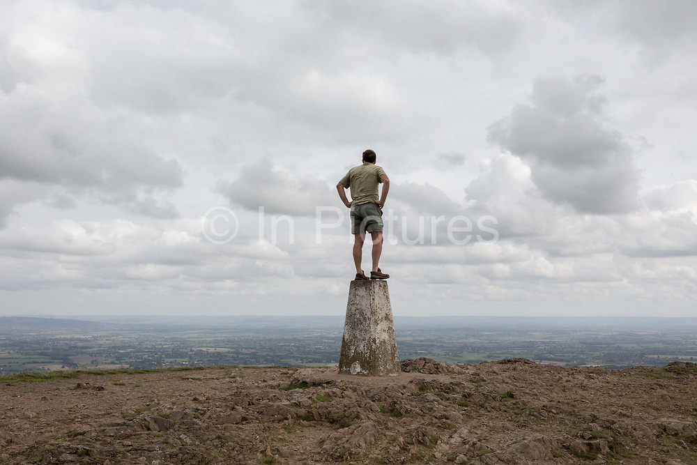 A hill climber stands on the top of the trig-point and looks across distant landscapes from the top of The Beacon, on 15th September 2018, in Malvern, Worcestershire, England UK. Worcestershire Beacon, also popularly known as Worcester Beacon, or locally simply as The Beacon, is a hill whose summit at 425 metres 1,394 ft[1] is the highest point of the range of Malvern Hills that runs about 13 kilometres 8.1 mi north-south along the Herefordshire-Worcestershire border, although Worcestershire Beacon itself lies entirely within Worcestershire. A triangulation station, also known as a triangulation pillar, trigonometrical station, trigonometrical point, trig station, trig beacon, or trig point, and sometimes informally as a trig, is a fixed surveying station, used in geodetic surveying and other surveying projects in its vicinity.