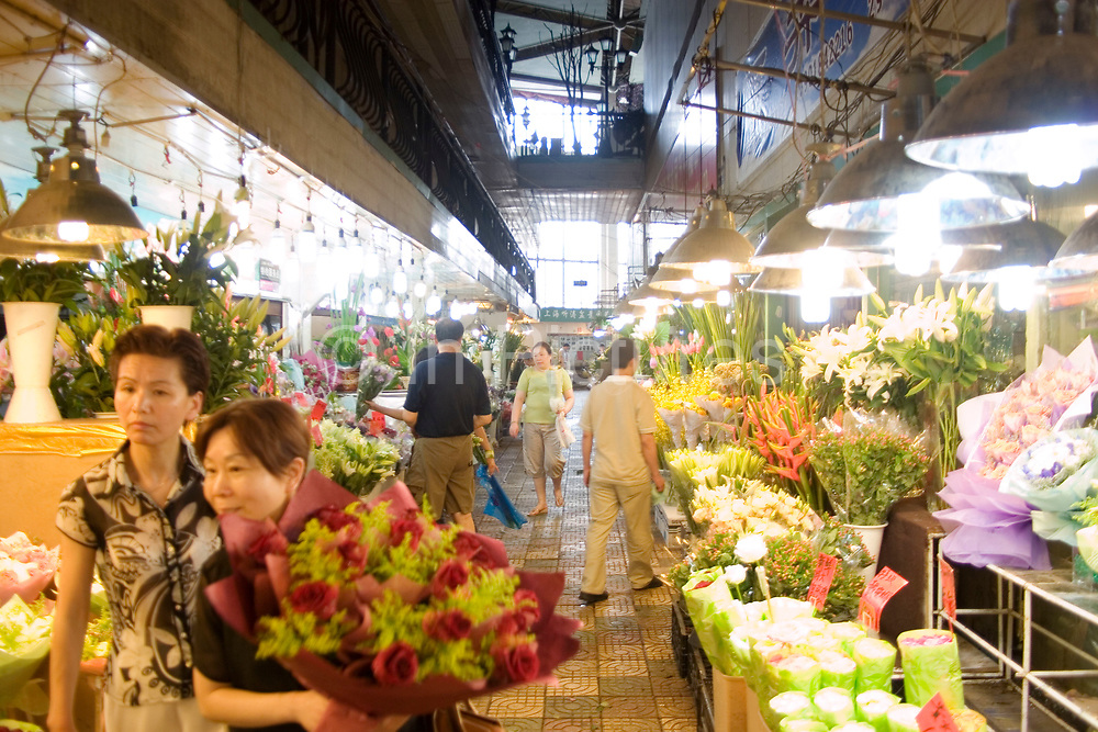 Shanghai's old flower market off Rejin Lu, downtown. This excellent flower market which sells fresh flowers on the ground floor and fake flowers upstairs is situated in an old communist party building. Sellers and arrangers work through the heat and cold in this exposed building, moving flowers at unbelievably low prices compared to this trade in the West.