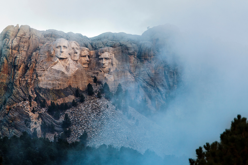 Mt. Rushmore is seen through clearing fog at sunrise from Iron Mountain road in the Black Hills in October.