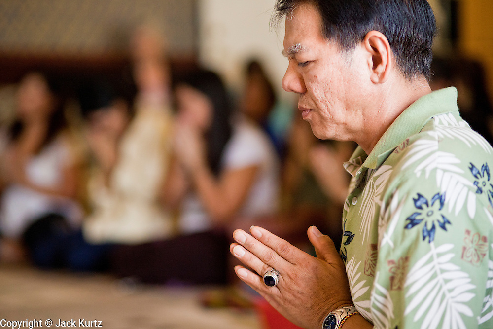 24 OCTOBER 2010 - CHANDLER, AZ: A man prays during the Ok Phansa services to mark the end of Buddhist Lent at Wat Pa, in Chandler, AZ, Sunday October 24. Buddhist Lent is a time devoted to study and meditation. Buddhist monks remain within the temple grounds and do not venture out for a period of three months starting from the first day of the waning moon of the eighth lunar month (in July) to the fifteenth day of the waxing moon of the eleventh lunar month (in October). Ok Phansa Day marks the end of the Buddhist lent and falls on the full moon of the eleventh lunar month, this year Oct 23. Wat Pa, a Thai Theravada Buddhist temple, celebrated Ok Phansa Day on October 24.    Photo by Jack Kurtz