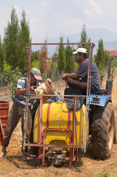 Vineyard workers on a tractor preparing for spraying. One man filling the tank with water. Kantina Miqesia or Medaur winery, Koplik. Albania, Balkan, Europe.