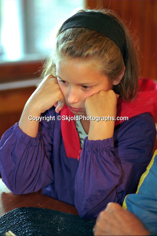 Sad girl age 9 sitting at the dinner table.  Cedarville  Michigan USA