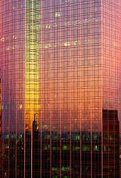 Stock photo of a colorful sunset reflecting off of the windows in a large high rise office building
