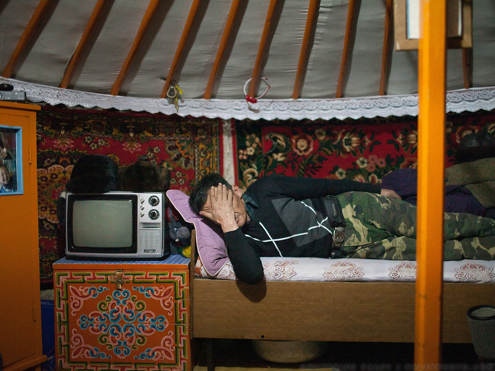 A herder takes a break after a day herding his animals. Many of his animals died because of the extreme cold. <br /> <br /> Road trip with a Jeep in the Gobi region.