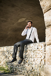 Businessman sitting and talking on mobile phone, Munich, Bavaria, Germany