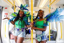 © Licensed to London News Pictures. 25/08/2019. London, UK. Mya and Minarje (L to R) travelling to Notting Hill Carnival in West London on London Underground train. Thousands of revellers take part in Notting Hill Carnival, Europe's largest street party and a celebration of Caribbean traditions and the capital's cultural diversity. Photo credit: Dinendra Haria/LNP
