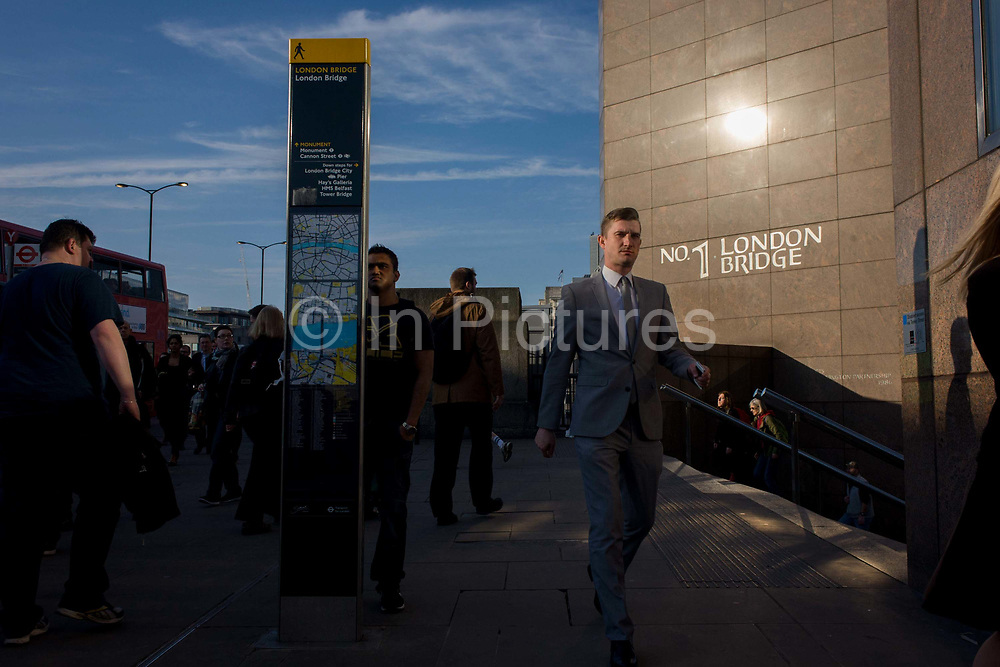 Londoners cross southbound over London Bridge during the evening rush hour. A young businessman walks past <br /> a city map pillar and the wall of some Eighties architecture at Number One, London Bridge. Commuters stride alongside others walking out of the City of London. There has been a crossing over the Thames here since the Romans first forded the river in the early 1st Century with subsequent medieval and Victorian stone bridges becoming an important thoroughfare from the City on the north bank, to Southwark on the south where transport hubs such as the mainline station gets commuters to the suburbs and satellite towns.