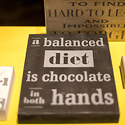 A humorous sign in a shop window in the historic center of Bruges, Belgium that reads: A balanced diet is chocolate in both hands. The region is famous for the quality of its chocolate.