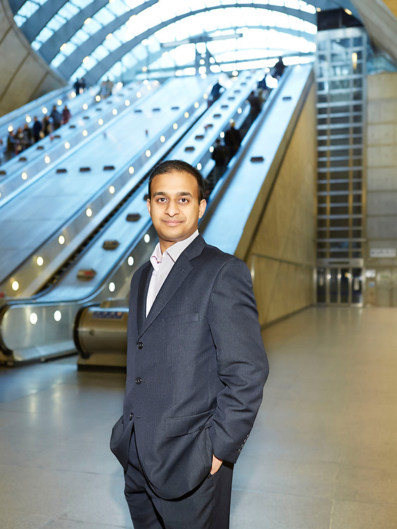 An Indian Businessman at Canary Wharf Tube station in London with escalator in background