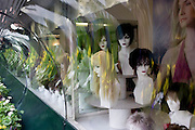 Wigs on bust models seen in the window of a retailer in central London.