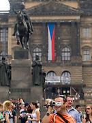 Tourist mit Videokamera am oberen Teil des Wenzelsplatzes in Prag mit dem Wenzelsdenkmal. Im Hintergrund die tschechische Nationalflagge und das Nationalmuseum.<br /> <br /> Tourist with a video camera at the upper part of Wenceslas Square with the Czech national flag, Wenceslav monument and the National Museum in the back.
