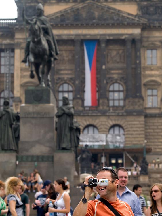 Tourist mit Videokamera am oberen Teil des Wenzelsplatzes in Prag mit dem Wenzelsdenkmal. Im Hintergrund die tschechische Nationalflagge und das Nationalmuseum.<br /> <br /> Tourist with a video camera at the upper part of Wenceslas Square with the Czech national flag, Wenceslav monument and the National Museum in the back.