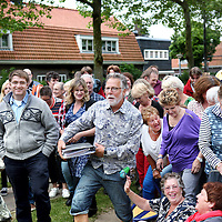 Nederland, Amsterdam , 11 juni 2013.<br /> Repetitie van de volksopra Tuindorp Oostzaan in Amsterdam Noord.<br /> De Volksopera Tuindorp Oostzaan bestaat uit beroemde aria's, duetten en koorzangen (van Puccini, Verdi, Bizet, Mozart etc.) Vertaald naar het Nederlands, niet letterlijk, maar naar een eigen verhaal, een libretto, waarin ook de geschiedenis van Tuindorp belicht wordt. <br /> <br /> Gekozen is al wel om de opkomst en ondergang van de NDSM-scheepswerf de rode draad in het verhaal te laten spelen. Dramatisch biedt dit vele mogelijkheden. Een groot deel van Tuindorp ontleende zijn/haar identiteit aan de scheepswerf. De geluiden van de werf waren tot diep in het dorp te horen. Na de grote bloeifase eind jaren 50, begin 60 van de vorige eeuw, volgde een roerige periode van stakingen, overnames en werkeloosheid. Het uiteindelijke faillissement van de werf, begin jaren 80, raakte Tuindorp tot in haar kern.<br /> <br /> Het libretto zal ook weer een liefdesverhaal bevatten. Grofweg zal de Volksopera dus gaan <br /> over het leven in Tuindorp, de sores en het geluk, tegen een achtergrond van opkomst & ondergang van de NDSM-scheepswerf, van de Watersnood van 1960, van de komst van de eerste emigranten (Turken vooral), de renovaties, het vertrek van de oude Tuindorpers en de komst van de nieuwe lichting. Over liefde, dood, jaloezie, misère en wederopstanding. En na anderhalf uur zal de goede afloop zegevieren: ondanks de tegenstellingen gaat Tuindorp Oostzaan eensgezind, hand in hand en in vrede de toekomst tegemoet. <br /> <br /> <br /> Foto:Jean-Pierre Jans