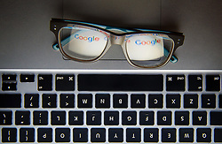The logo of internet search engine Google reflected in a pair of glasses.